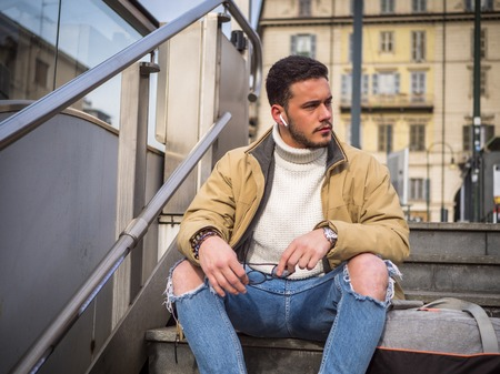 Handsome bearded young man sitting outdoors in urban environment looking to a side