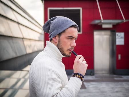 Young man vaping, smoking e-cigarette outdoor, wearing wool sweater and beanie cap