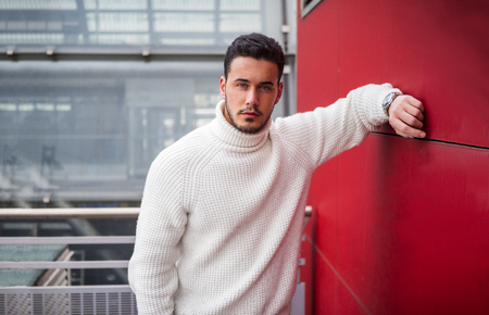 Stylish trendy young man standing outdoor against red wall, looking confindent at camera Imagens