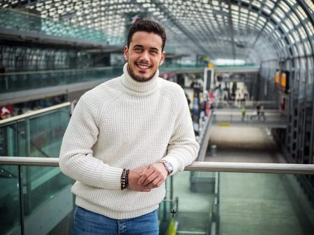 Attractive young man inside modern building, station or airport or office complex Imagens