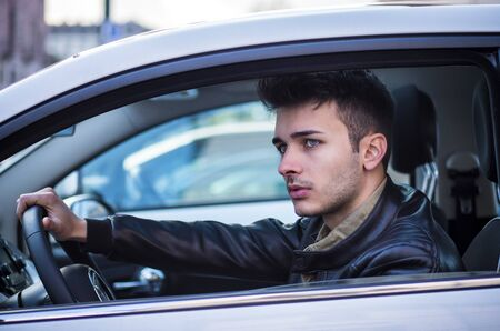 Handsome blue eyed young man sitting in his car, looking away Standard-Bild