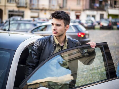 Portrait of attractive man in white shirt entering his new stylish polished car outdoor in city street Standard-Bild