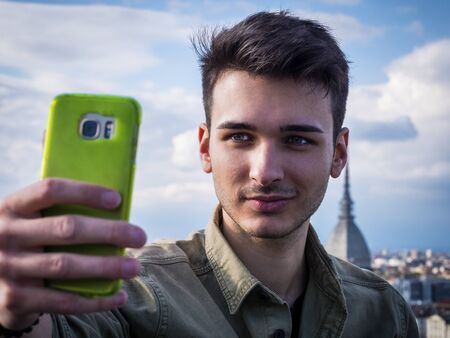 Portrait of young attractive man in winter coat using cell phone to take selfie photo outdoor in European city, Turin, Italy