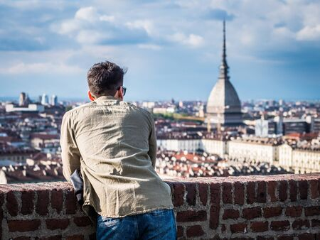 Young ma posing in Turin, Italy with Mole Antonelliana, the symbol of the city Imagens