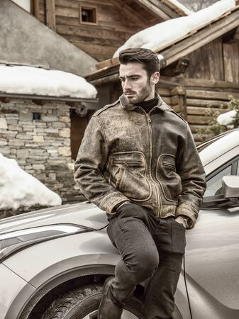Young man standing leaning on SUV car. Snowy road and mountain on background