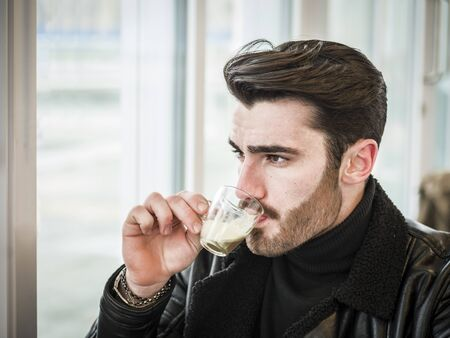 Attractive Man Drinking Coffee while Sitting in a Bar Table with Serious Expression Imagens