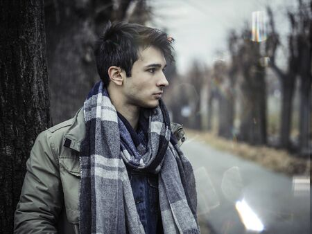 Handsome young man outdoor in winter fashion, wearing dark jacket and woolen scarf in city park