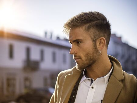 Handsome trendy blond man standing outdoor in European city setting with elegant old historic building behind Imagens
