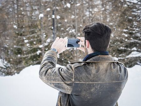 Handsome young man using smarpthone to take photographs of the landscape, while posing among snowy woods in the mountain Standard-Bild