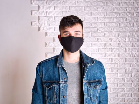 Contagious young male in denim jacket and medical mask looking at camera while standing against white wall