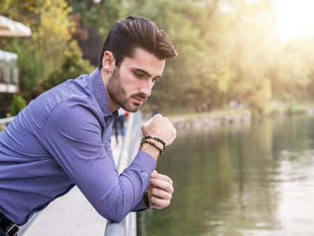 Portrait of contemplative handsome brown haired young man, with short beard, wearing shirt beside picturesque river or lake, looking away to a side during fall Standard-Bild