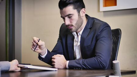 Handsome businessman sitting in his office, talking to client and showing him options on tablet PC screen.