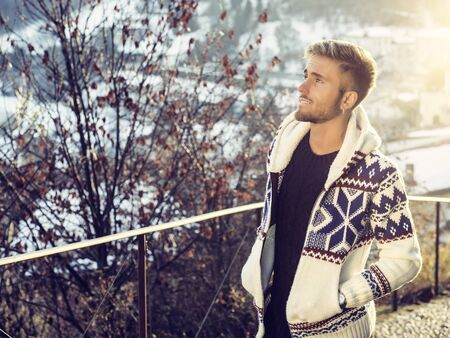 Handsome young man outdoor in winter fashion, wearing black coat and woolen scarf in city park Imagens