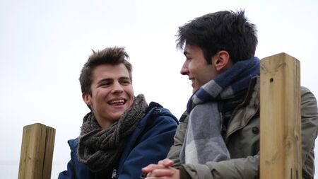 From below view of young men in winter clothing talking while chilling outdoors, smiling and laughinig Imagens