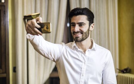 Handsome smiling young man doing selfie with smartphone at home in living room. Horizontal indoors shot Imagens