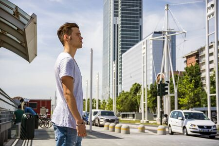 Profile shot of attractive young man in city by a street, looking away, outdoor