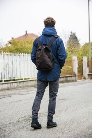 Teenage boy walking alone in city street with backpack, seen from the back Standard-Bild
