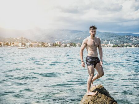 Handsome muscular young man standing on a sea boulder by the beach, relaxed, shirtless, ready to bathe
