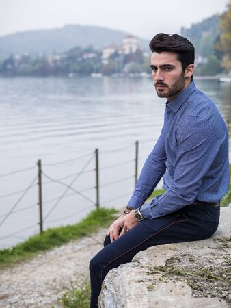 Portrait of contemplative handsome brown haired young man, with short beard, wearing shirt beside picturesque river or lake, looking away to a side during fall Imagens