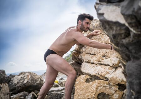 Handsome, muscular, shirless climber, looking in camera and climbing stone wall Standard-Bild