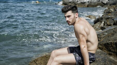 Handsome muscular young man sitting on a rocky beach, relaxed, shirtless, looking away Imagens