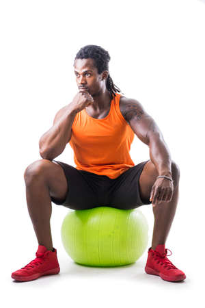Muscular black man sitting on inflatable fitness ball, looking at camera, isolated on white background
