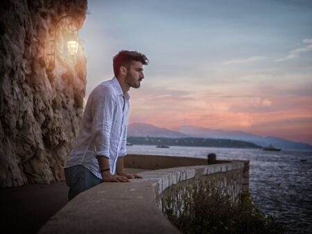 Side view of male in white shirt leaning on border and admiring sea while standing on embankment near rough cliff with lantern against sundown sky Standard-Bild