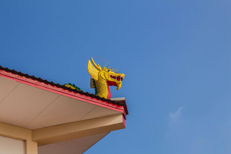 Statue of a dragon on temple roof photo
