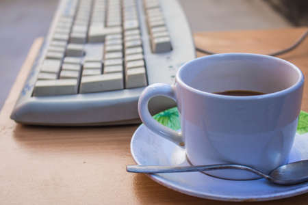 Cup of coffee on the table and keyboard photo