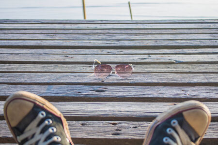 Glasses and shoes on a wooden floor. photo