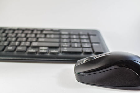 The wireless mouse is placed above the keyboard. photo