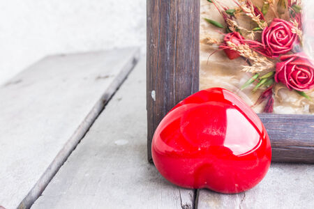 Red heart and frame on a wooden photo