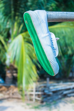 sully: Sneakers hang on a wooden railing.