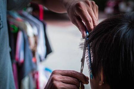haircuts: hand clippers haircuts for men in the community. Stock Photo