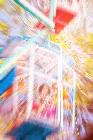 Children on a rotating Ferris wheel with the blue sky.