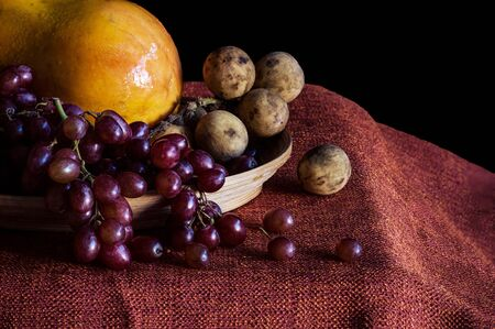broaching: Grapes and papaya on the table with a black background.
