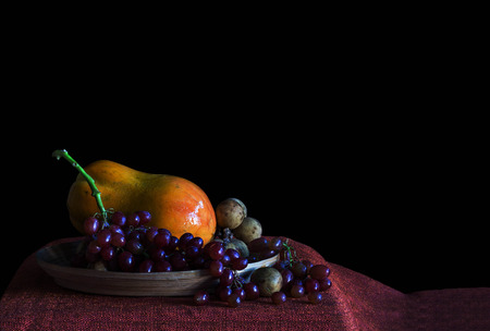 broaching: Grapes and papaya on a tray with a black background.