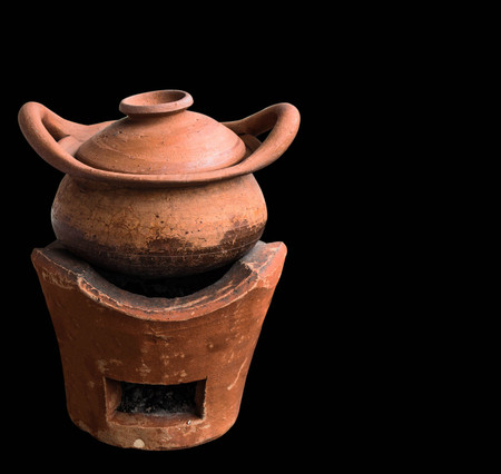 Old clay pot on the stove with a black background.