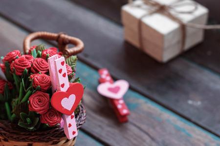 Heart-shaped i czerwone kwiaty w koszyku na drewnianych. Zdjęcie Seryjne