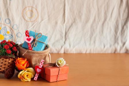Dar torby i kosze róż na drewnianej podłodze. Zdjęcie Seryjne