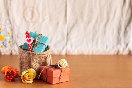 Torby na prezenty i róże na drewnianym stole. Zdjęcie Seryjne