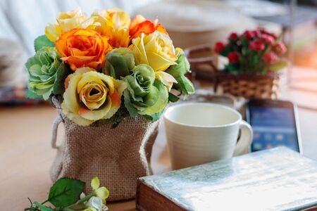 Colorful roses in a vase on table at office.