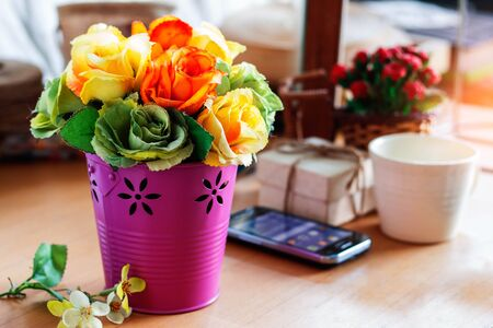 Colorful roses in a vase on the desk.