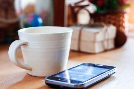 Filiżanka kawy i prezent na biurku.