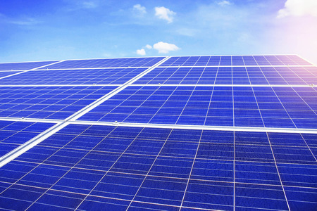 Solar panels on a blue sky with light during the day.