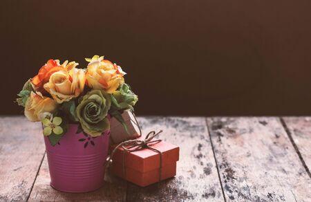 uprzejmości: Vase of roses with a gift on the table. Zdjęcie Seryjne