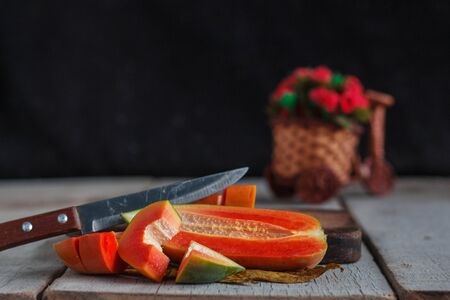 Papaya slices and knife on old wooden floor.