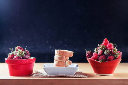 Roll cake and strawberries in the plate on a wooden table. Stock Photo