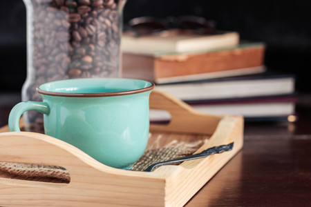 cup of coffee on a wooden tray with a book at the desk. Stock Photo
