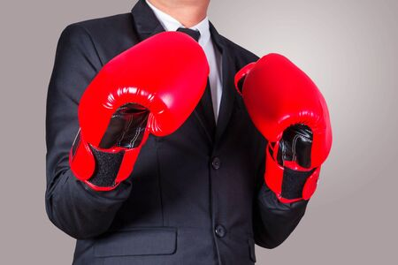 padding: business man puts on boxing gloves with a business fight. Stock Photo